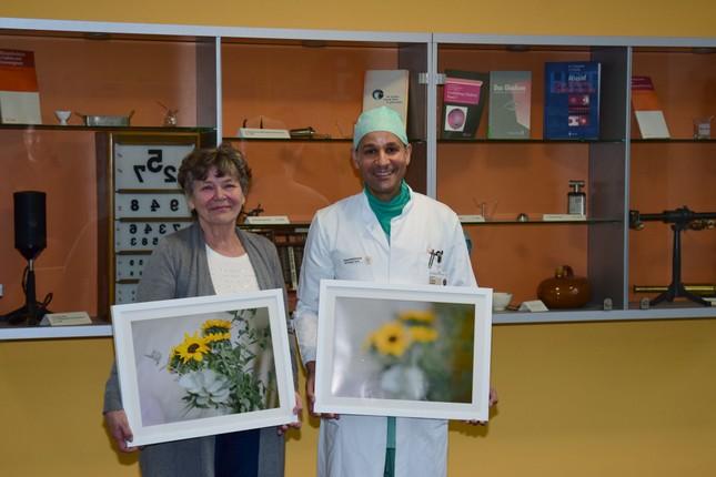 Patientin Jutta Poisel und Oberarzt Prof. Frederik Raiskup halten zwei Bilder der DGFG-Fotoausstellung in den Händen. Die linke Aufnahme zeigt, wie verschwommen die Sicht bei einer degenerierten unteren Hornhautschicht ist.